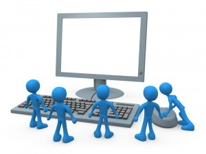 Group Of Tiny Blue Employees Standing In Front Of A Computer Keyboard And Looking Up At A Flat Screen Lcd Monitor Screen While One Person Operates The Mouse Clipart Illustration Graphic